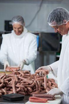 Butchers processing sausages