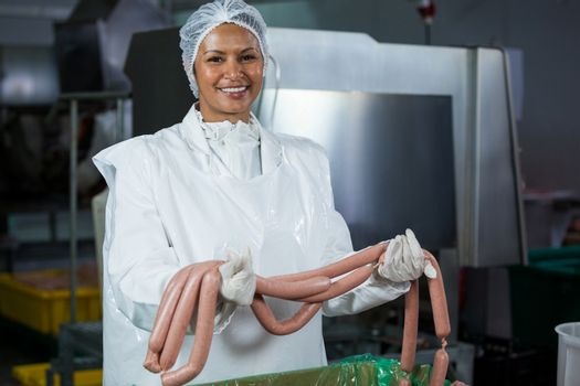 Female butcher holding sausages