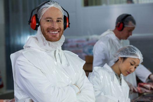 Smiling butcher in protective headphones
