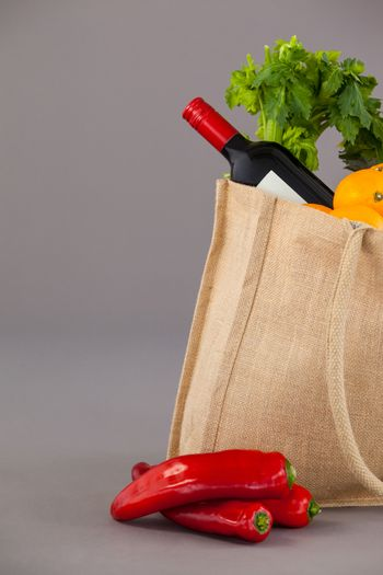 Wine bottle and vegetables in grocery bag