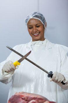 Female butcher sharpening her knife