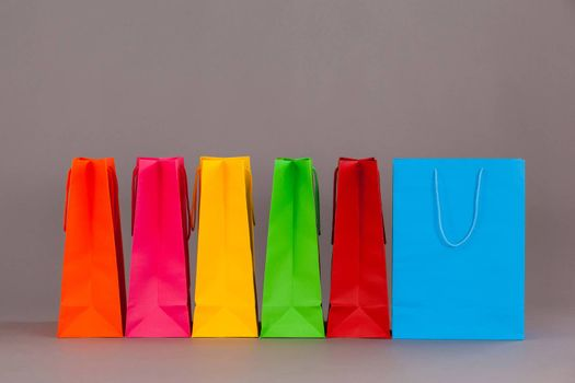Colorful shopping bags against grey background