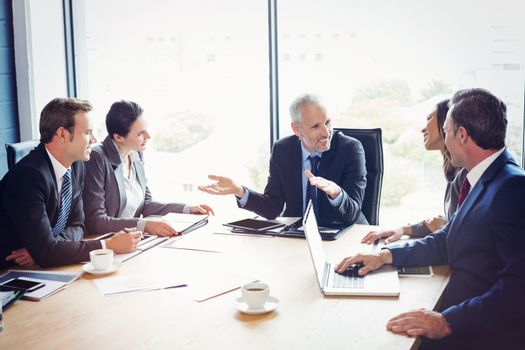 Happy businesspeople discussing in conference room