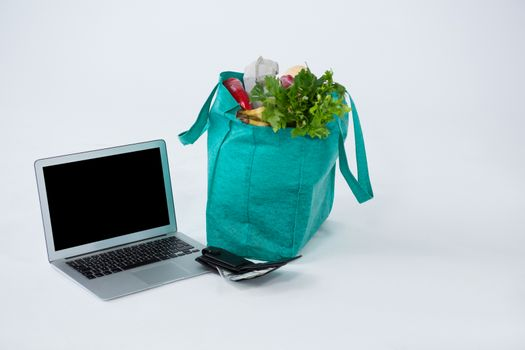 Grocery bag with wallet and laptop