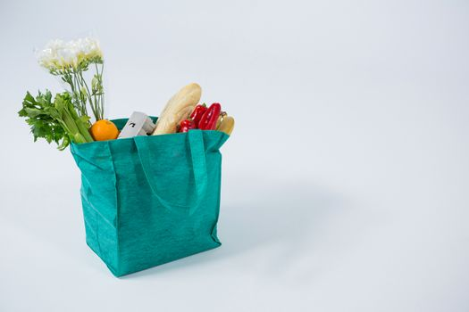 Bread loaf and vegetables in grocery bag