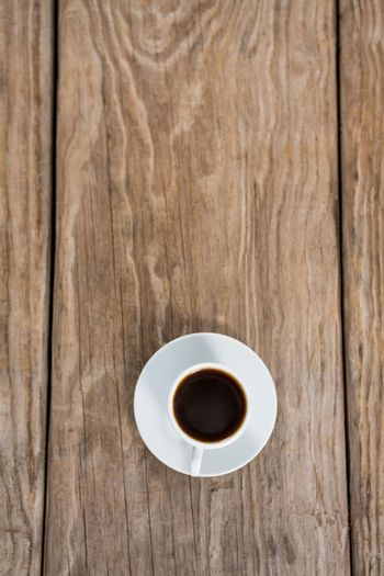 Cup of coffee with saucer on a wooden table