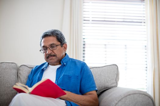 Senior man with spectacles reading a novel