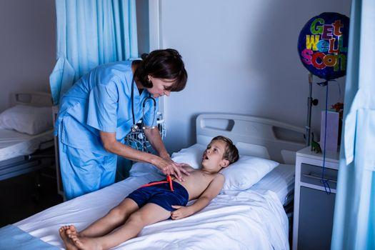 Female doctor examining abdomen of patient