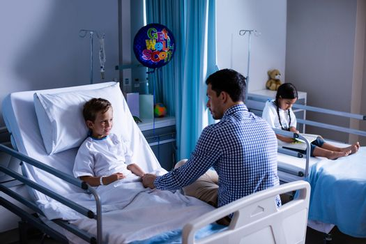 Father consoling his son during visit in ward