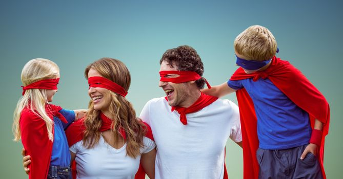 Family in superhero costumes against blue background