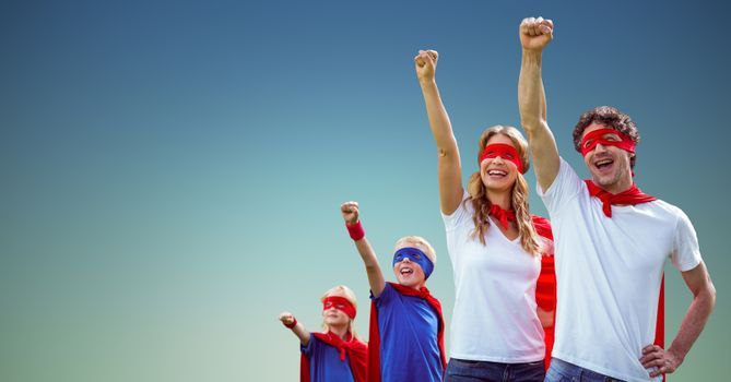 Family in superhero costumes standing with arms raised
