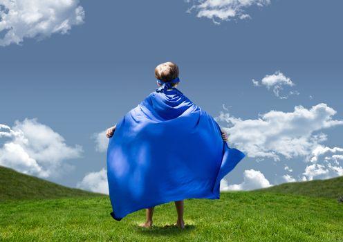 Boy in superhero costume standing on grasslands against sky in background