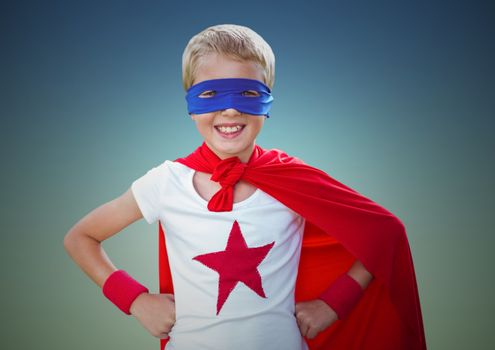 Composite of smiling kid wearing red cape and blue mask standing with hand on hip against clear sky
