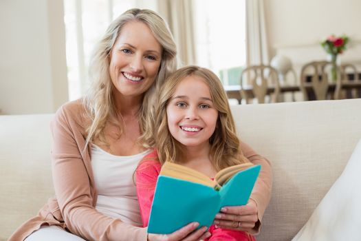 Mother and daughter reading a novel on the couch