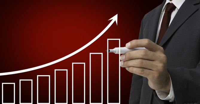 Businessman drawing upward trend graph with marker