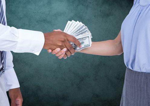Businessman bribing partner while shaking handsagainst teal background