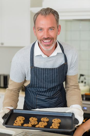 Man holding a cookies in baking tray at kitchen