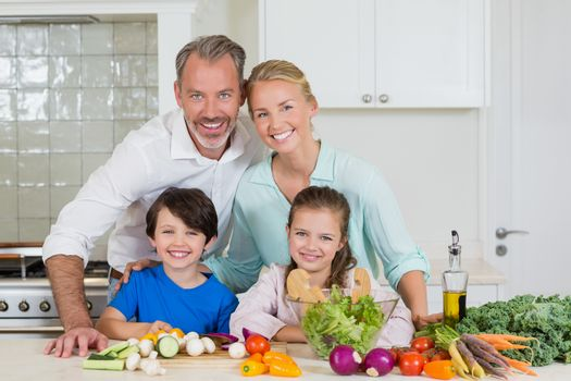 Portrait of parents and their two kids standing in kitchen