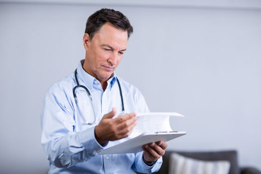 Male doctor reading reports