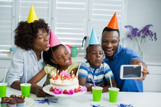 Happy family taking selfie from mobile phone while celebrating birthday party at home