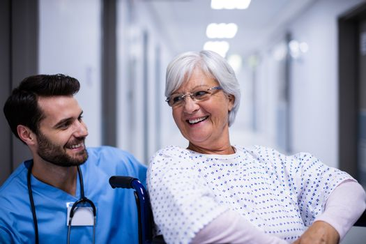 Male doctor interacting with senior patient on wheel chair in the corridor