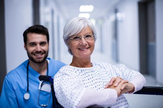 Portrait of male doctor and female senior patient smiling in the corridor