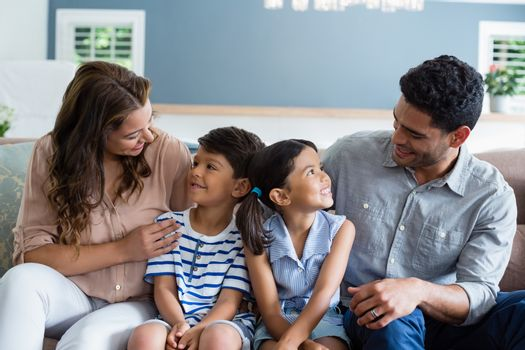 Parents and kids interacting on sofa in living room at home