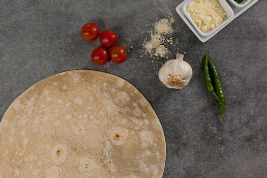 Pizza dough and ingredient on grey background