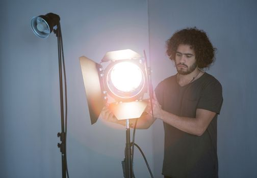 Male photographer adjusting spotlight