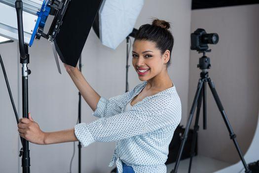 Female photographer adjusting spotlight