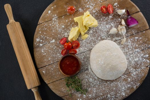 Rolling pin with pizza dough and flour on rolling board