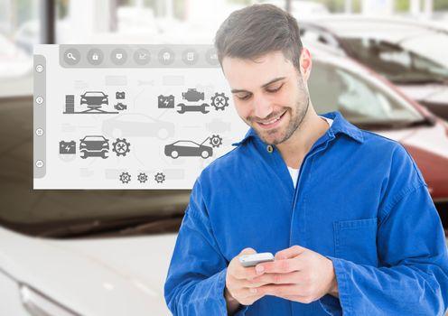 Happy automobile mechanic using mobile phone
