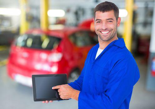 Happy automobile mechanic holding a digital tablet