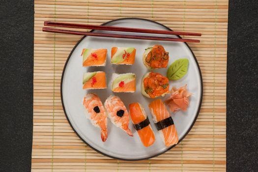Assorted sushi set served with chopsticks on sushi mat against black background