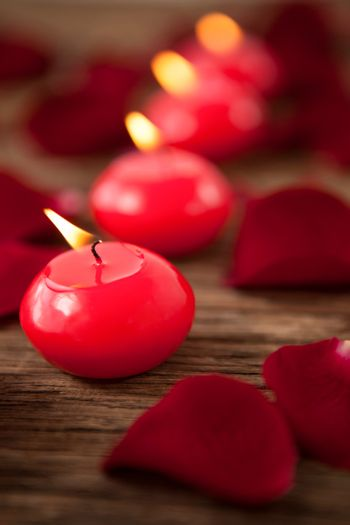Red wax candles surrounded with rose petals