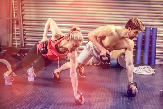 Couple doing push up with dumbbells