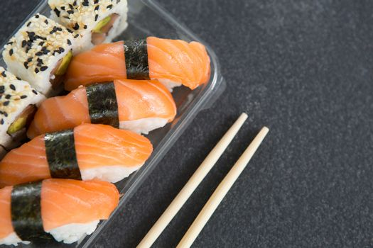 Close-up of sushi rolls with salmon in plastic container