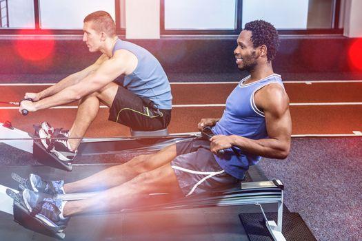 Muscular men using rowing machine