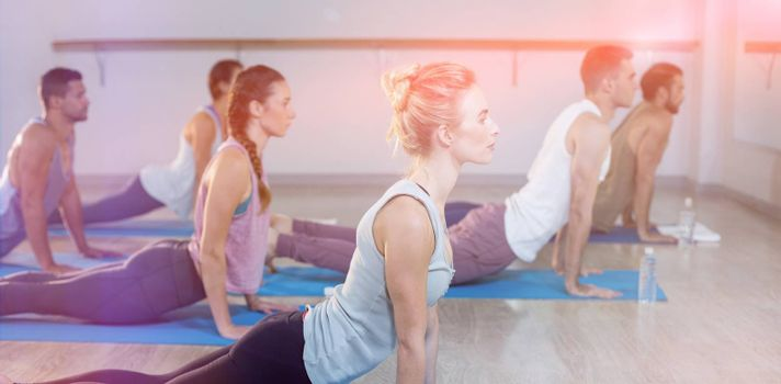 Side view of people performing yoga in gym