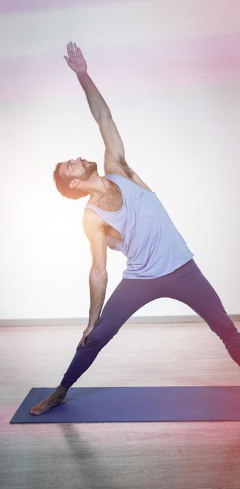 Man doing extended triangle pose in fitness studio