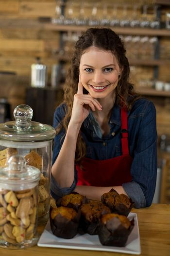 Waitress serving a cup cake at counter