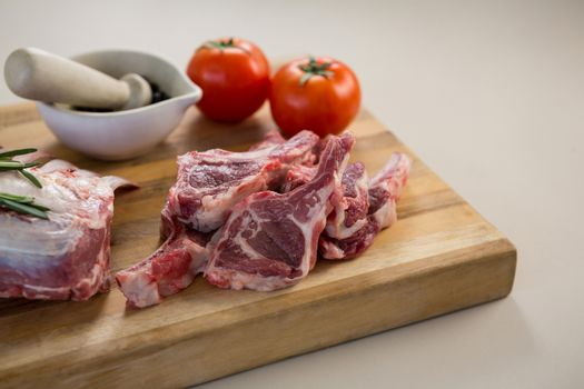 Rib chop, stone grinder and tomatoes on wooden board