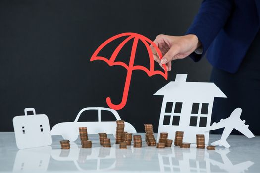 Businesswoman protecting her wealth with umbrella