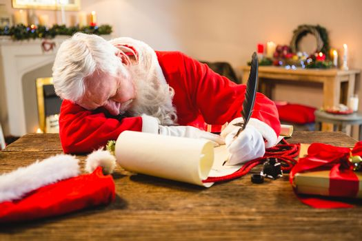 Santa claus sleeping at table while writing a letter with a quill