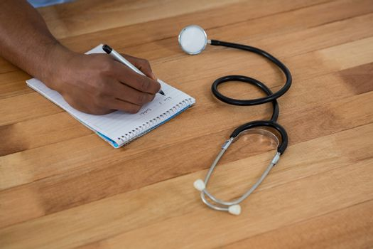 Doctor writing prescription on notepad