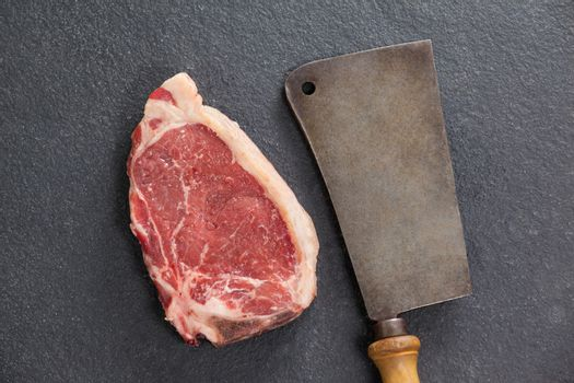 Sirloin chop and cleaver against black background