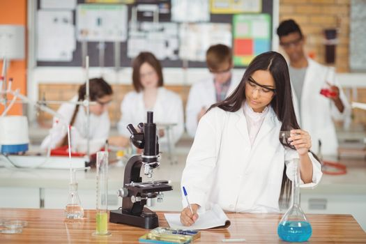 School girl writing in journal book while experimenting in laboratory
