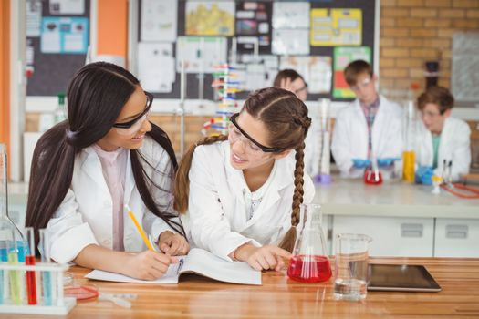 School girls writing in journal book while experimenting in laboratory at school