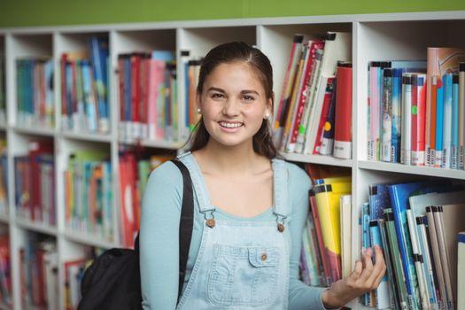 Portrait of happy schoolgirl selecting book in library at school