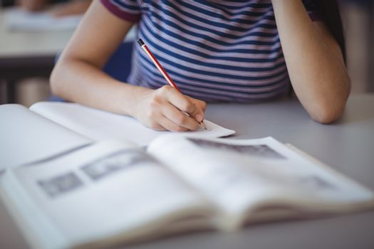 Mid section of schoolgirl studying in classroom at classroom